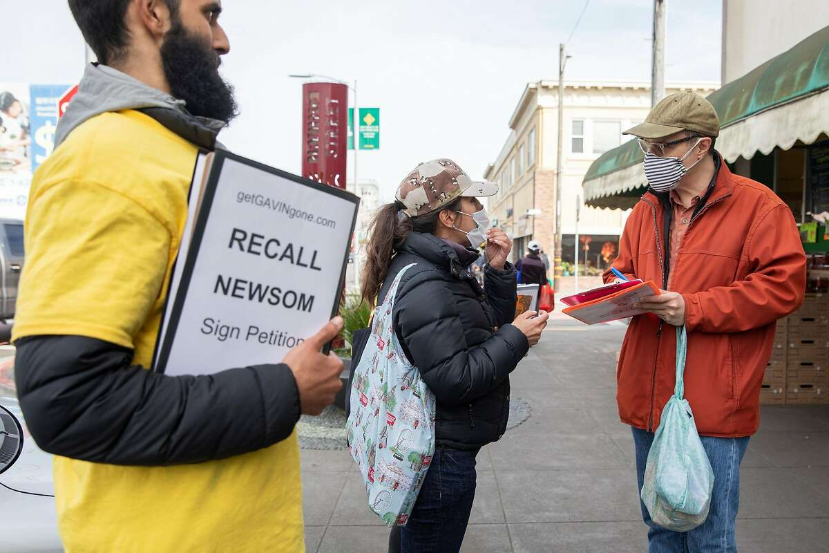 Carlo Mastrogiacomo of San Francisco signs a petition to Recall Gavin Newsom as Recall Gavin Newsom campaign volunteers work to gather signatures from customers outside of 22nd & Irving Market in San Francisco, Calif. Tuesday, March 2, 2021. The effort to recall Gov. Gavin Newsom is gaining momentum, and supporters are rushing to collect more signatures before the March 17 deadline.