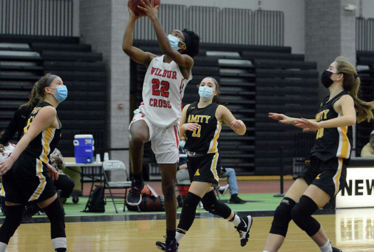 Wilbur Cross' Dejah Middleton (22) drives to basket past three Amity Regional defenders during a girls basketball game on Tuesday, March 2, 2021 in New Haven, Conn.
