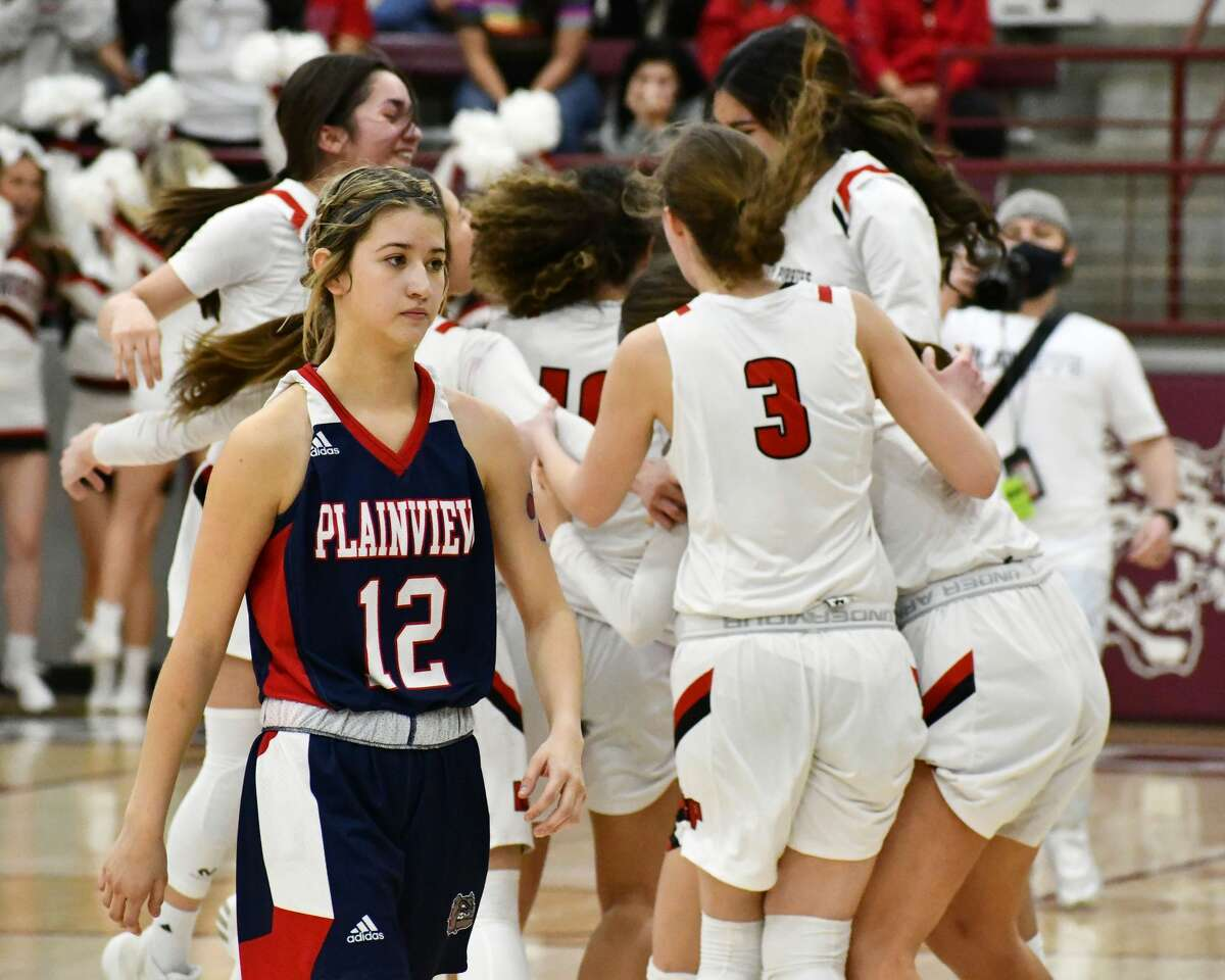 Plainview's Majik Esquivel walks in front of celebrating Lubbock-Cooper players at the conclusion of the Class 5A Region 1 championship game on Tuesday at Littlefield.
