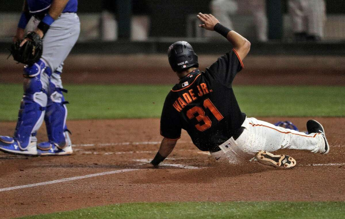 Outfielder LaMonte Wade Jr., acquired from the Minnesota Twins before spring training, slides across home for the Giants' only score of the game in the sixth inning against the Dodgers.
