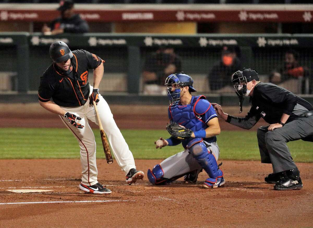 Darin Ruf (33) spins out of the way of a close pitch as the San Francisco Giants played the Los Angeles Dodgers at Scottsdale Stadium in Scottsdale, Ariz., on Tuesday, March 2, 2021.