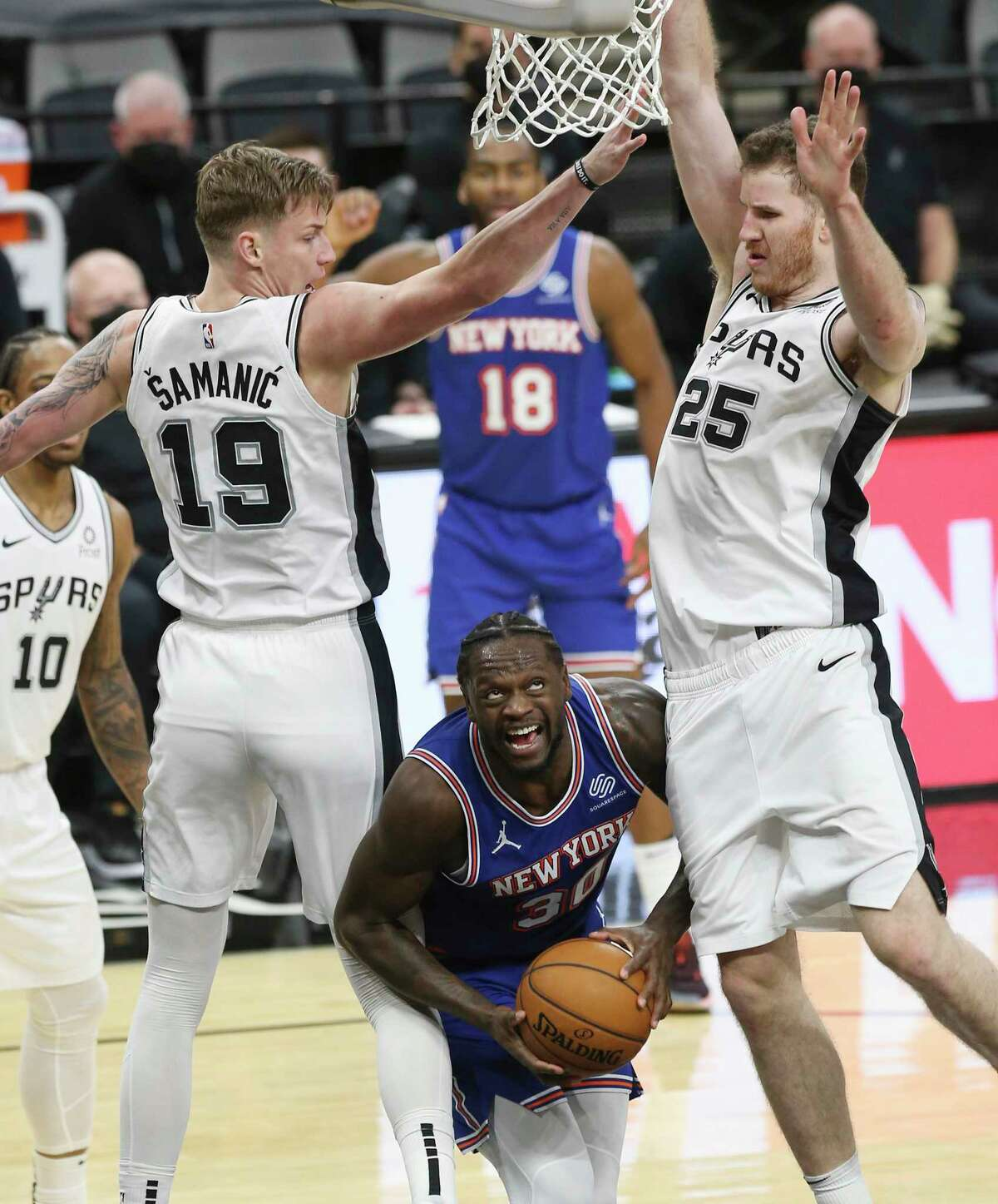 Spurs' Luka Samanic (19) and Jakob Poeltl (25) hover over New York Knicks' Julius Randle (30) at the AT&T Center on Tuesday, Mar. 2, 2021.