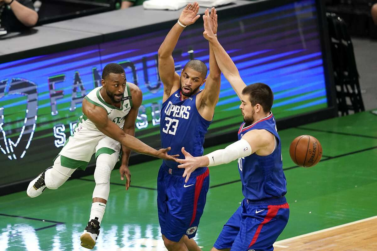 Boston Celtics guard Kemba Walker, left, passes the ball between Los Angeles Clippers forward Nicolas Batum (33) and center Ivica Zubac in the first quarter of their game in Boston.