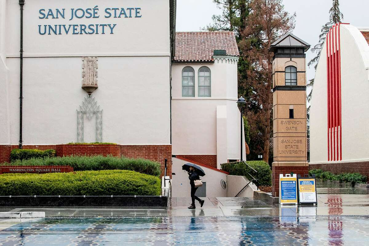 A person walks with an umbrella past San Jose State University's campus in January. The school now faces three lawsuits in the wake of its handling of sexual-abuse allegations against former director of sports medicine Scott Shaw.