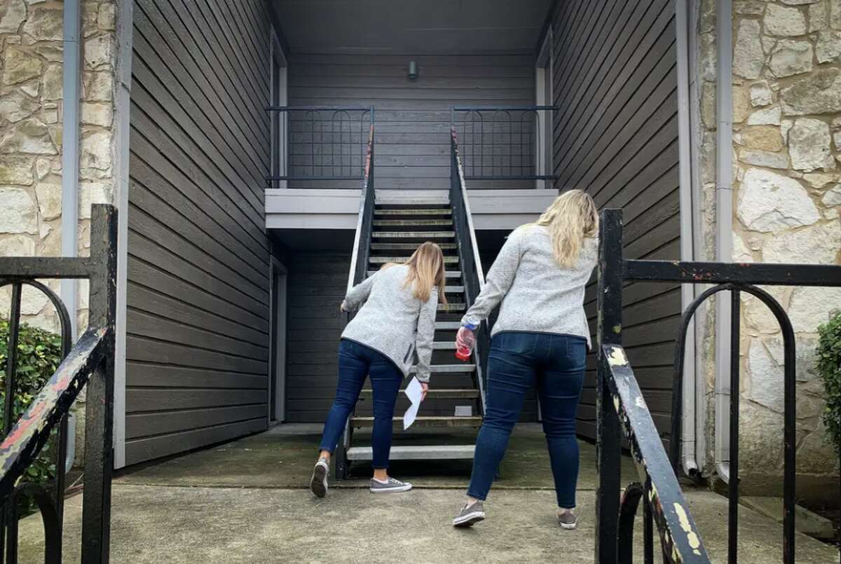 Brandee Brandt (left) and Emily Countryman look for apartment numbers at one of 15 stops they will make during a day of home visits to find kids who are disengaged during remote learning.