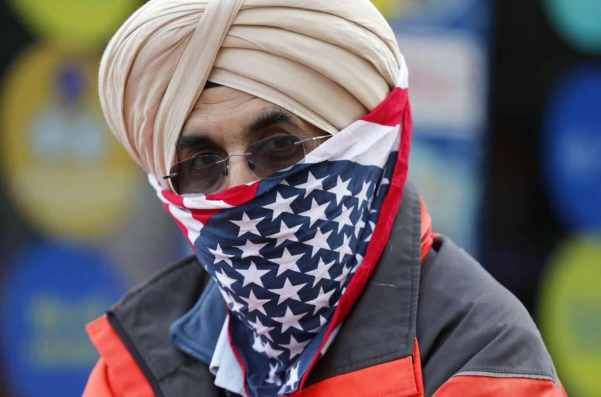 A postal worker wears an American flag as a face covering to protect against COVID-19 in London on Jan. 29, 2021.