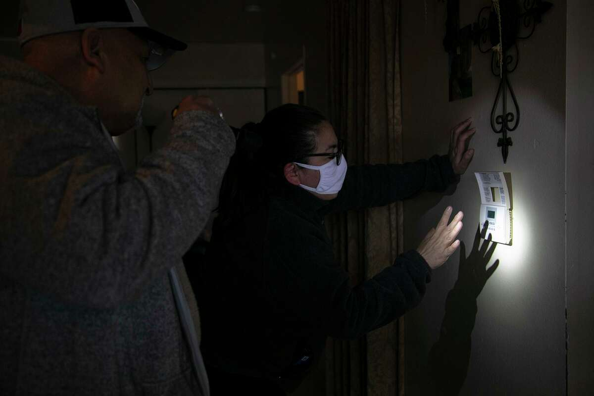 Community advocate Queta Rodriguez helps a man, who is legally bling, set his thermostat once power was restored at his apartment during last month's freeze. The city of San Antonio should be better coordinating with neighborhoods to facilitate disaster response.