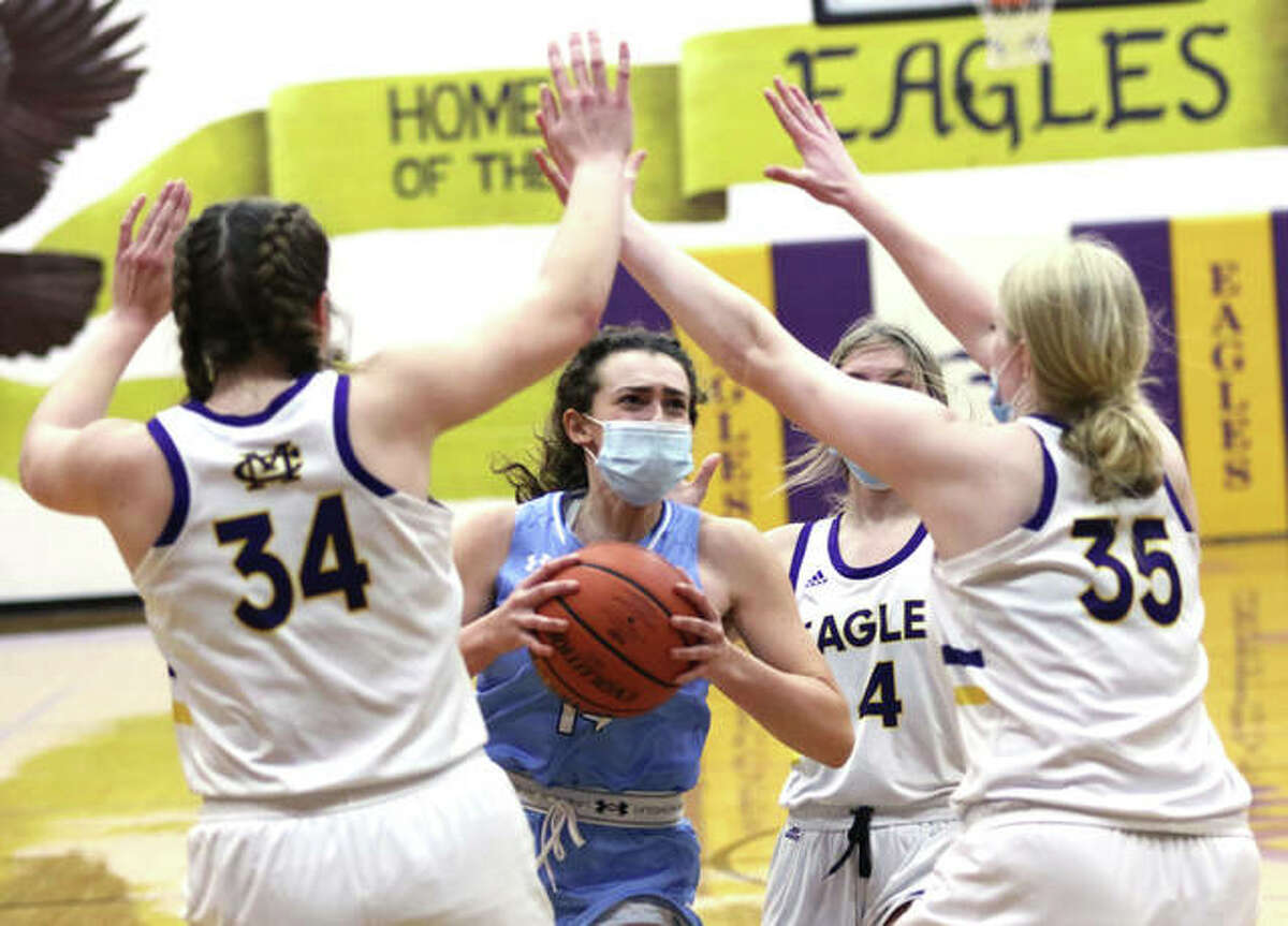 Jersey's Chloe White takes the ball to a CM 6-foot double-team of Jackie Woelfel (34) and Claire Christeson (25) during a Feb. 22 game in Bethalto. On Tuesday, White scored a career-high 27 points in the Panthers' MVC win over Mascoutah, while CM stayed unbeaten in the conference with a victory over Waterloo.