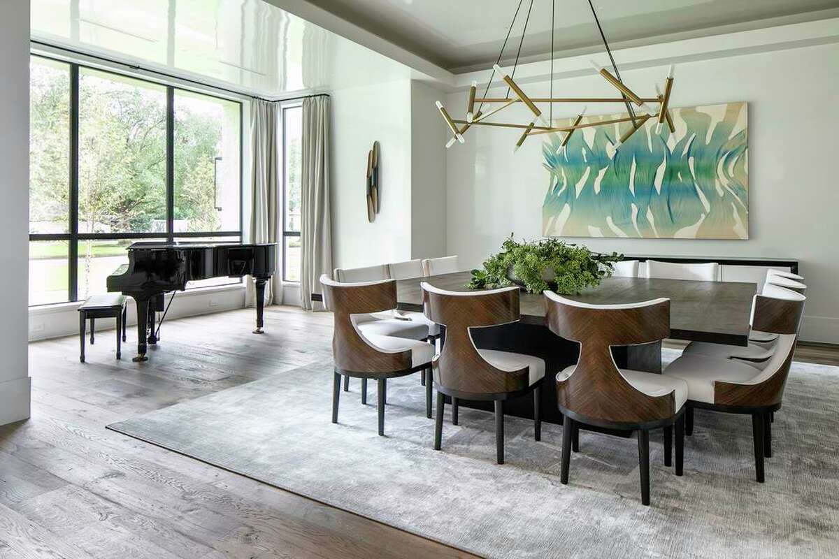 A baby grand piano shares space with an oversize square table in he dining room.