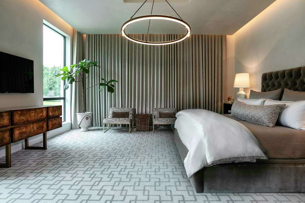The primary bedroom suite is filled with soft neutral colors. The top of motorized draperies are hidden in pockets underneath a dropped ceiling with cove lights.