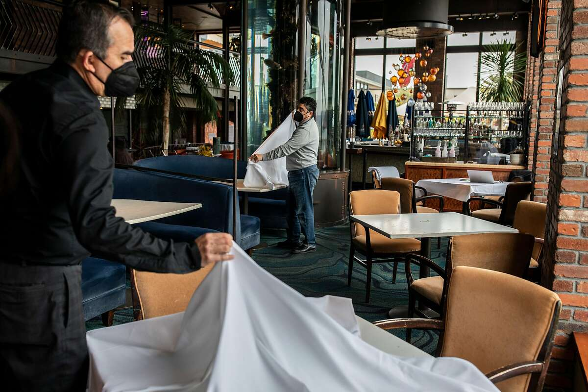 At Waterbar in S.F., Ricardo Torres (left) and Rich Troiani put tablecloths on tables as restaurants prepare for indoor dining in S.F. and other Bay Area counties.