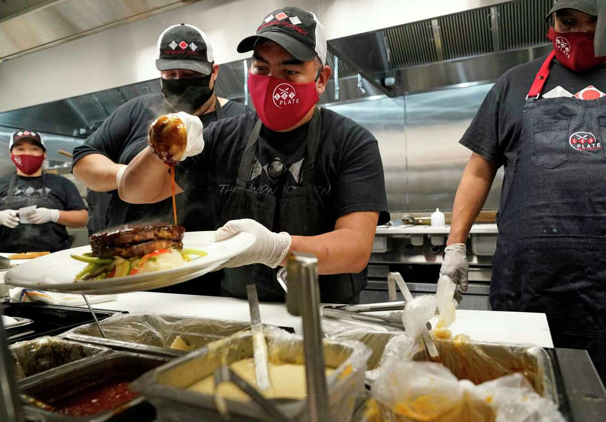 Eduardo Francisco garnishes a plate as he and others all wear masks as they work at The Union Kitchen in Katy.