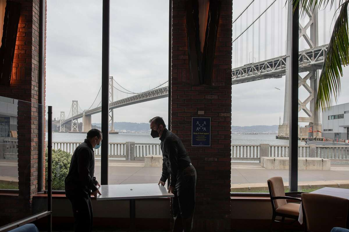At Waterbar in S.F., tables are put back in place as restaurants prepare for indoor dining in S.F. and other Bay Area counties.