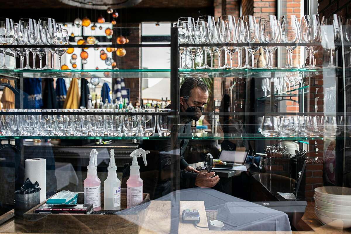 Ricardo Torres, assistant general manager at Waterbar in San Francisco, tidies up the bar. San Francisco is making new adjustments that ease pandemic restrictions for bars, restaurants and other activities.