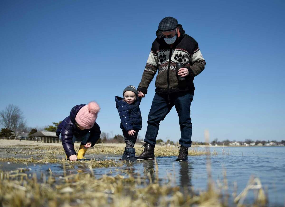 Greenwich's Noel Rideout and his kids, Alexandra, 3, and Holden, 1, play along the shoreline at Greenwich Point Park in Old Greenwich, Conn. Wednesday, March 3, 2021. After a frigid Tuesday, high temperatures Wednesday approached 50 degrees.