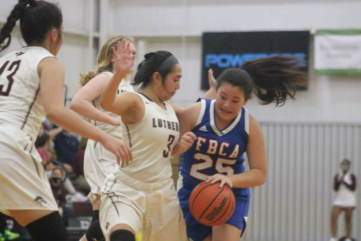 Maddy Gay finds her route blocked by San Antonio Lutheran's Kellie Khlot, the game's leading scorer, during their playoff game in San Antonio Tuesday night.