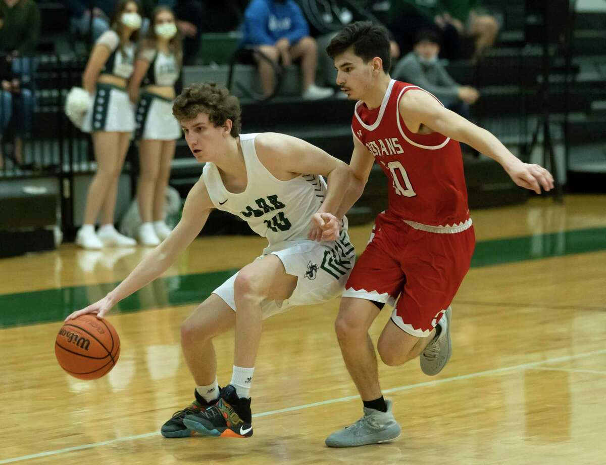Kingwood Park Brendan Tynan (10) dribbles the ball while under pressure from Cleveland guard Zaid Roldan (10) during the fourth quarter of a 20-5A District basketball game at Kingwood Park High School, Wednesday, Feb. 10, 2021, in Kingwood.