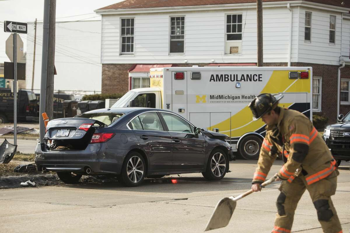 Members of the City of Midland Police and Fire Departments secure the scene of a collision at the intersection of Buttles and McDonald Streets Wednesday, March 3, 2021 in Midland. (Katy Kildee/kkildee@mdn.net)