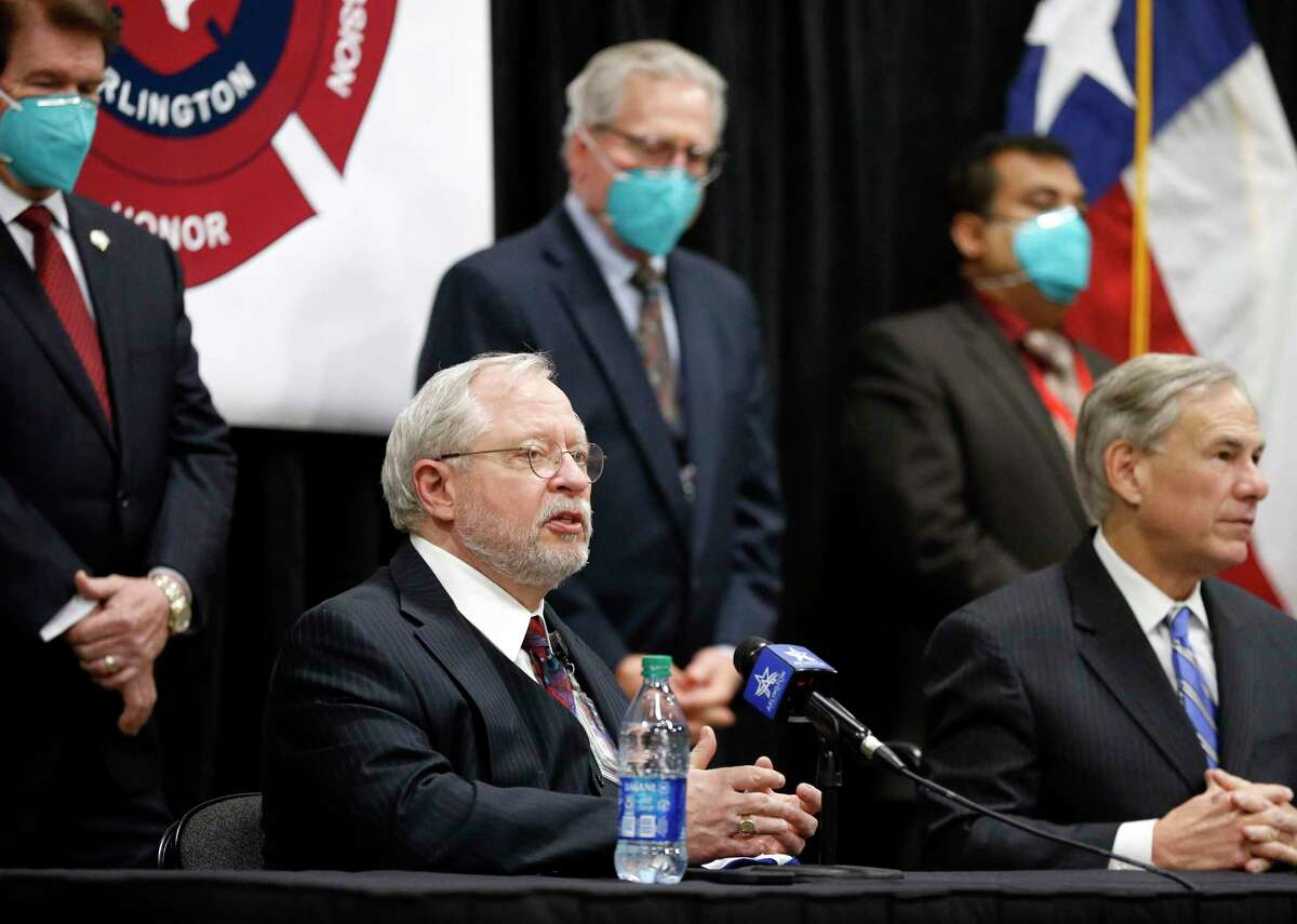 Texas Department of State Health Servcies Commissioner John Hellerstedt, MD makes remarks during Texas Governor Greg Abbott's (right) press conference at the Esports Stadium Arlington & Expo Center, a mass COVID-19 vaccination site in Arlington, Texas, Monday, January 11, 2021. (Tom Fox/The Dallas Morning News)