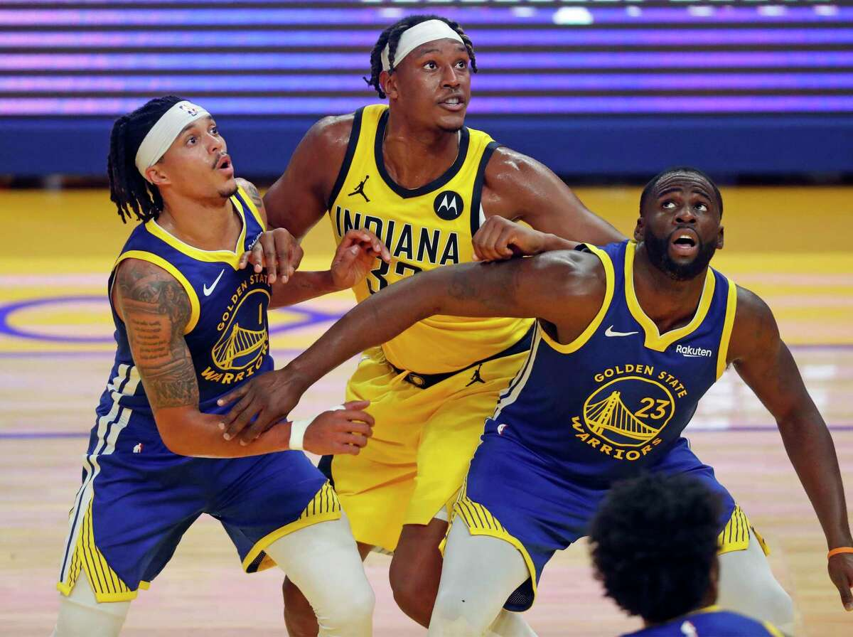 Golden State Warriors' Draymond Green and Damion Lee box out Indiana Pacers' Myles Turner in 2nd quarter during NBA game at Chase Center in San Francisco, Calif., on Tuesday, January 12, 2021.