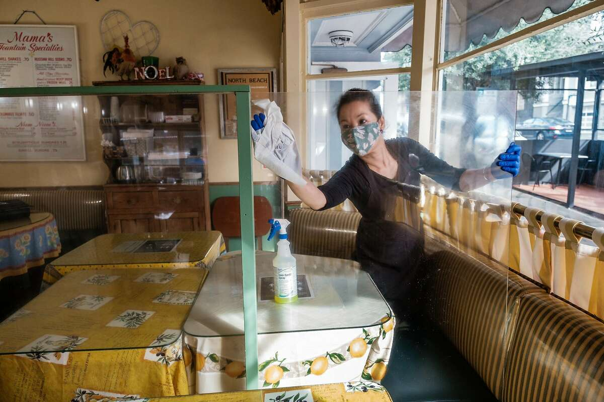 Top: Lily Chen cleans the indoor dining space at Mama's in North Beach as they prepare to offer indoor seating to guests starting tomorrow in San Francisco on Wednesday, March 3, 2021. Officials announced that San Francisco, Santa Clara and Napa counties are advancing from the most-restrictive purple tier to the red tier in California's coronavirus reopening system.