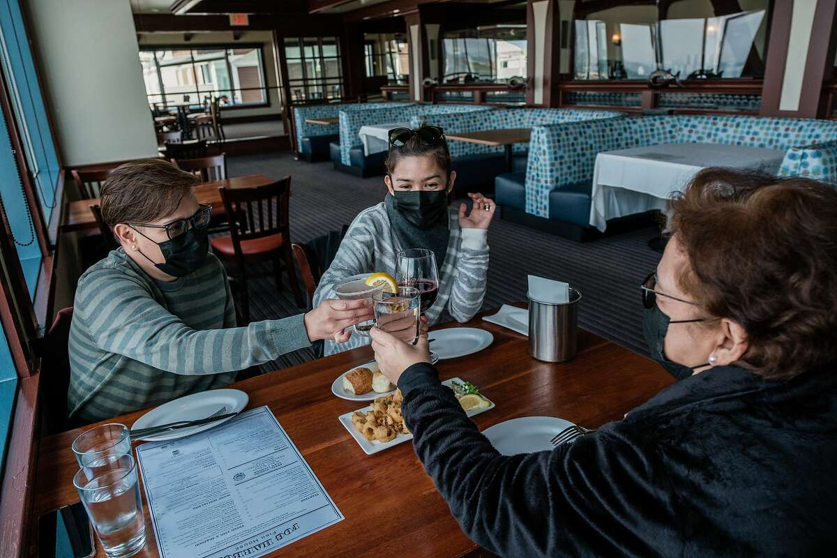 Rica Joson, Nancy Joson and Nikki Gacias cheers to celebrate the reopening of indoor a dining at Fog Harbor Fish House on Pier 39 in San Francisco this week.