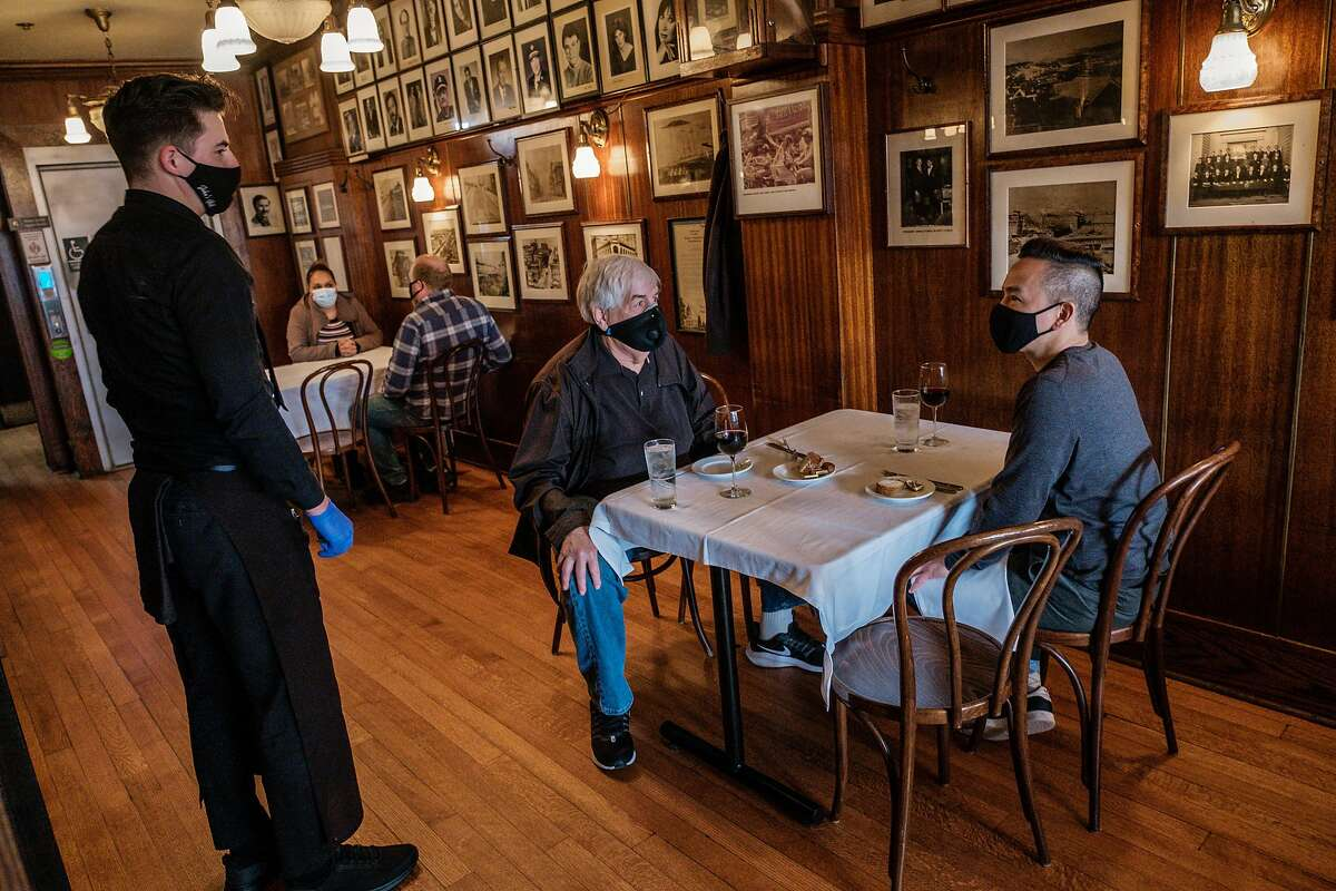 Howard Golden and Sean Kulanet place their lunch order at John's Grill in San Francisco, newly reopened to indoor dining.