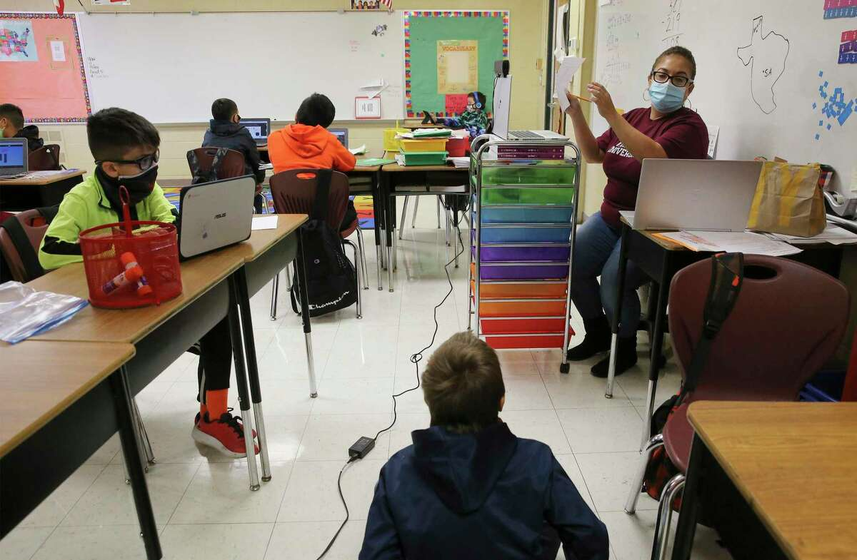 Third-grade teacher Valerie Sanchez (right) offers instruction to in-class and online students on Thursday, Dec. 3, 2020. Students at Pearce Elementary at Southside ISD attend a combination of online and in-person class learning.