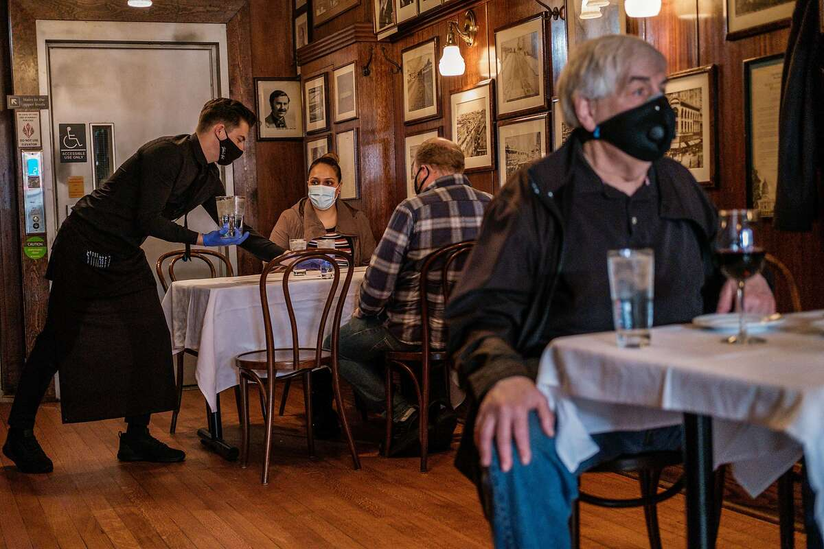 A waiter serves water to patrons dining indoors at John's Grill in San Francisco on Wednesday, March 3, 2021. Officials announced that San Francisco, Santa Clara and Napa counties are advancing from the most-restrictive purple tier to the red tier in California's coronavirus reopening system.