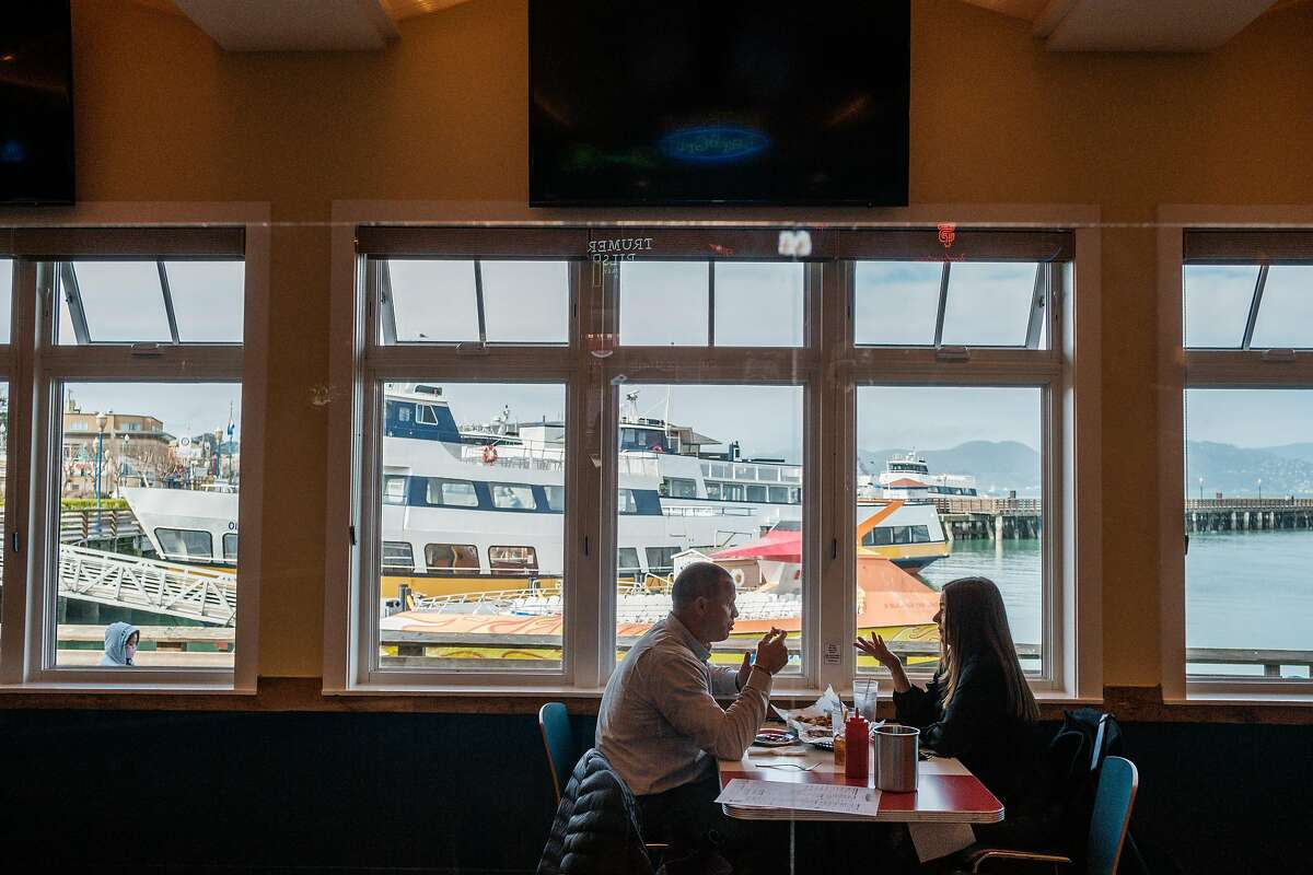 Joseph Daly and Andrea Brown dine indoors at Wipeout on Pier 39 in San Francisco on Wednesday, March 3, 2021. Officials announced that San Francisco, Santa Clara and Napa counties are advancing from the most-restrictive purple tier to the red tier in California�s coronavirus reopening system.