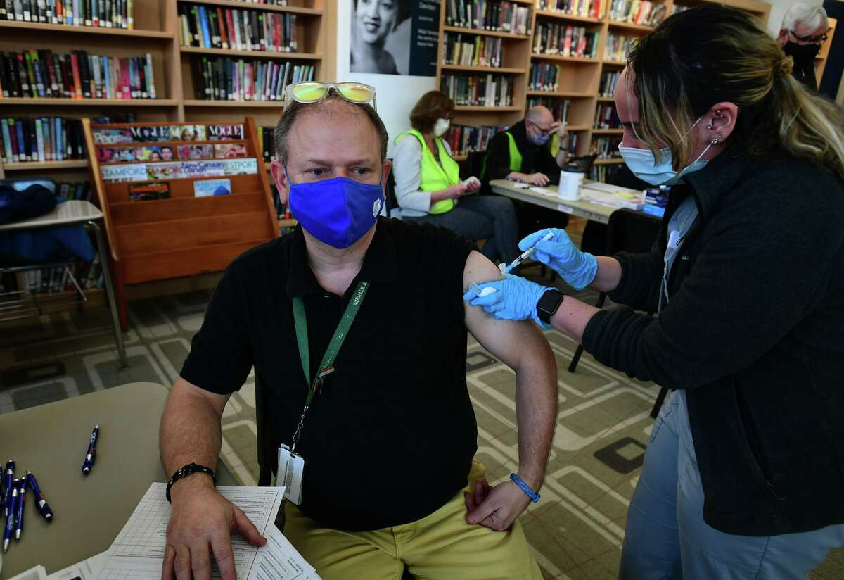 Norwalk High School physics teacher Glenn Couture receives a coronavirus shot from NCHC nuse Jessica Sanchez on Wednesday as local officials announce a vaccination clinic hosted by the City of Norwalk for Norwalk Public Schools teachers and educators.