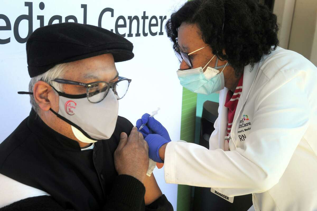 Nurse Marie St. Jean administers a COVID-19 vaccination to Bishop John Diamond of the Cathedral of Faith during a news conference in front of St. Vincent's Medical Center, in Bridgeport, Conn. Feb. 26, 2021. Nine black and Latino clergy members from various Bridgeport ministries received vaccinations at the Friday event.