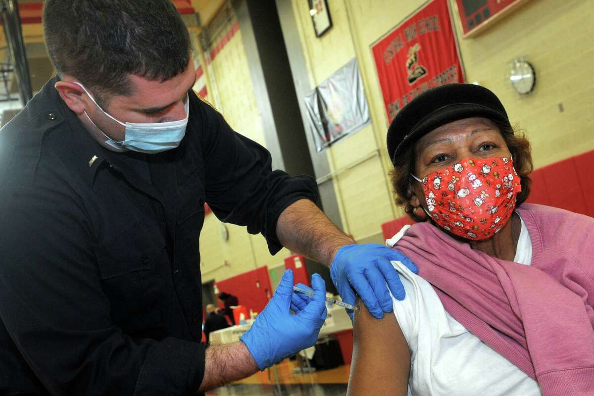 Lt. Ken Benedict of the Bridgeport Fire Department administers a COVID-19 vaccine to Lucy Gagliano, of Bridgeport, at the weekly vaccination clinic held in the gymnasium of Central High School in Bridgeport, Conn. Feb. 10, 2021.