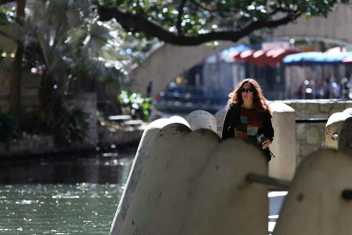 A woman enjoys the spring-like weather on the River Walk.