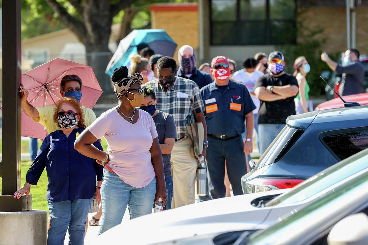 People wear masks while waiting in line to vote on the first day of early voting at Universal City Library on Tuesday, Oct. 13, 2020.