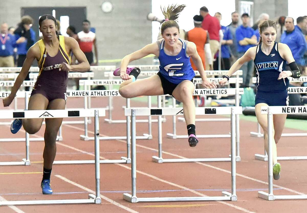 New Haven Connecticut - February 22, 2020: Tess Stapleton of Fairfield Ludlowe H.S. wins the girls 55-meter hurdles finals, center, against second-place finisher Kayla Clark of St. Joseph H.S., left, and third place finisher Shelby Dejana of Wilton H.S., right, during the CIAC State Open Indoor Track Championship Saturday at the Floyd Little Athletic Center in New Haven.
