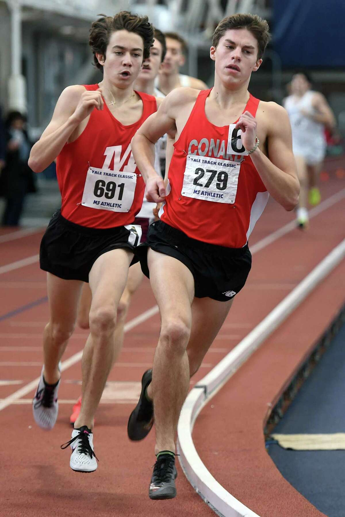 Aidan Puffer (left) of Manchester tries to keep pace with Gavin Sherry of Conard in the boys one mile run at the Yale Interscholastic Track Classic at Coxe Cage in New Haven on January 11, 2020.