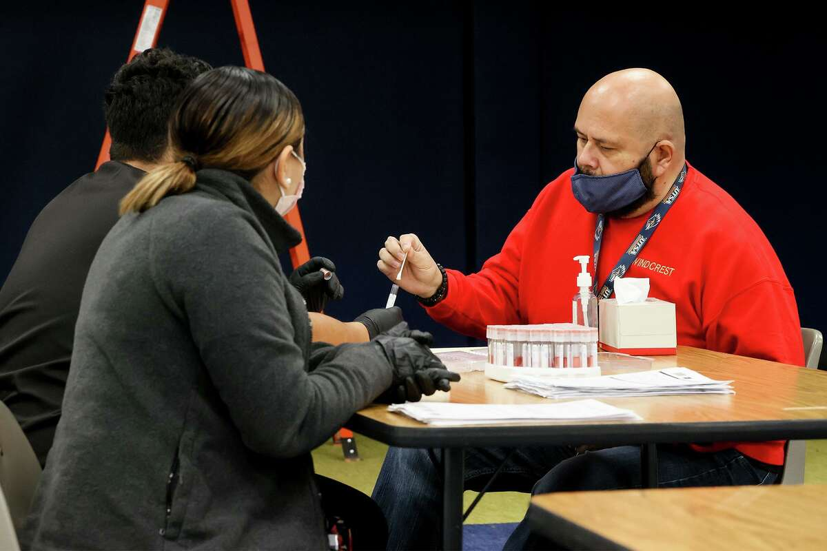 Angel Navarro, left, and Gloria Olivo with Community Labs watch as Elolf Elementary fifth-grade teacher Robert Ozuna takes a self-administered COVID-19 test at the school in Converse on Jan. 21. Judson ISD collaborated with Community Labs to offer the testing to all staff and students free of charge on 30 campuses.