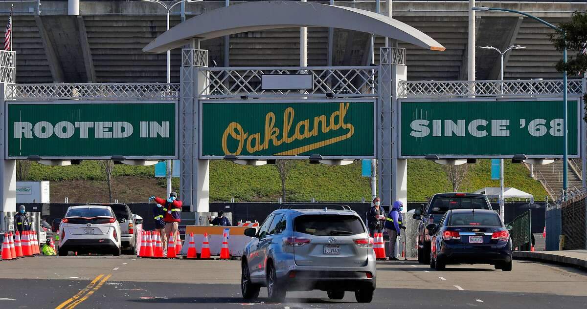 Drivers approach the main gates on 66th Avenue as Pfizer COVID-19 vaccines were administered to the public for the first day of mass vaccinations at the Oakland Coliseum in Oakland, Calif., on Tuesday, February 16, 2021.