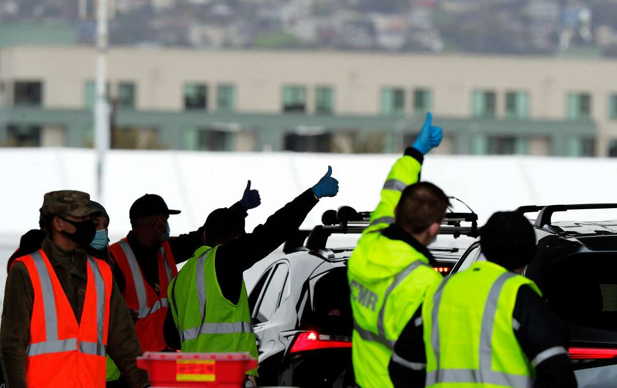 Healthcare workers signal that their row of cars is finished as Pfizer COVID-19 vaccines were administered to the public for the first day of mass vaccinations at the Oakland Coliseum in Oakland, Calif., on Tuesday, February 16, 2021.
