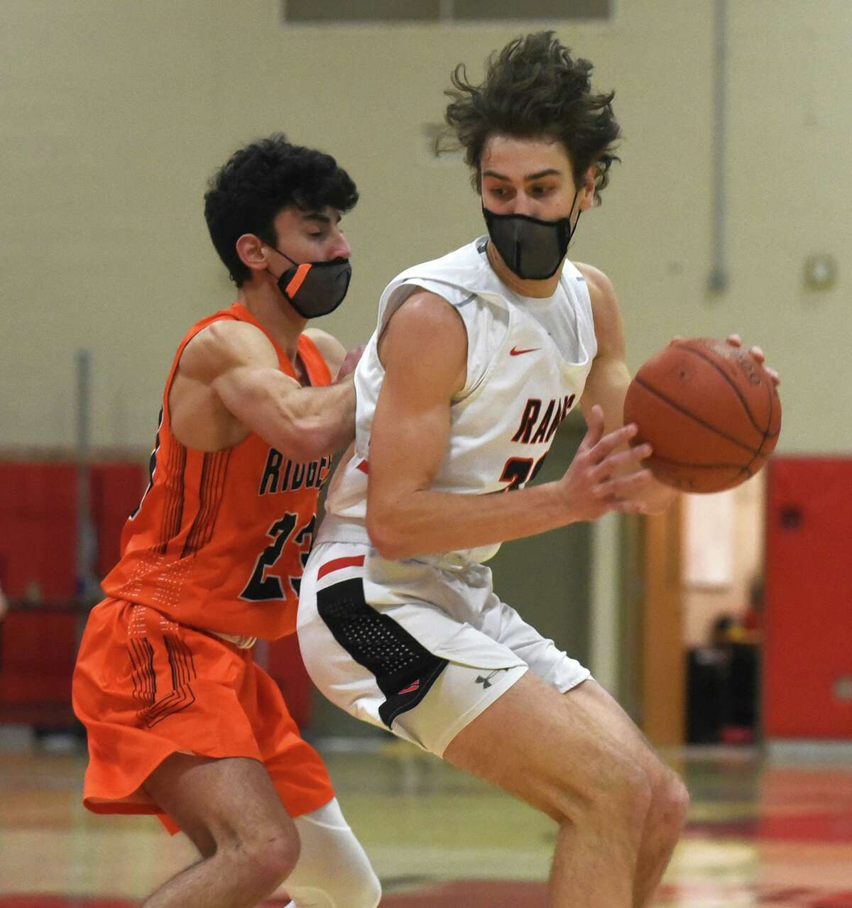 New Canaan's Leo Magnus (20) drives against Ridgefield's Ben Klotz (23) during a boys basketball game at New Canaan High School on Wednesday.