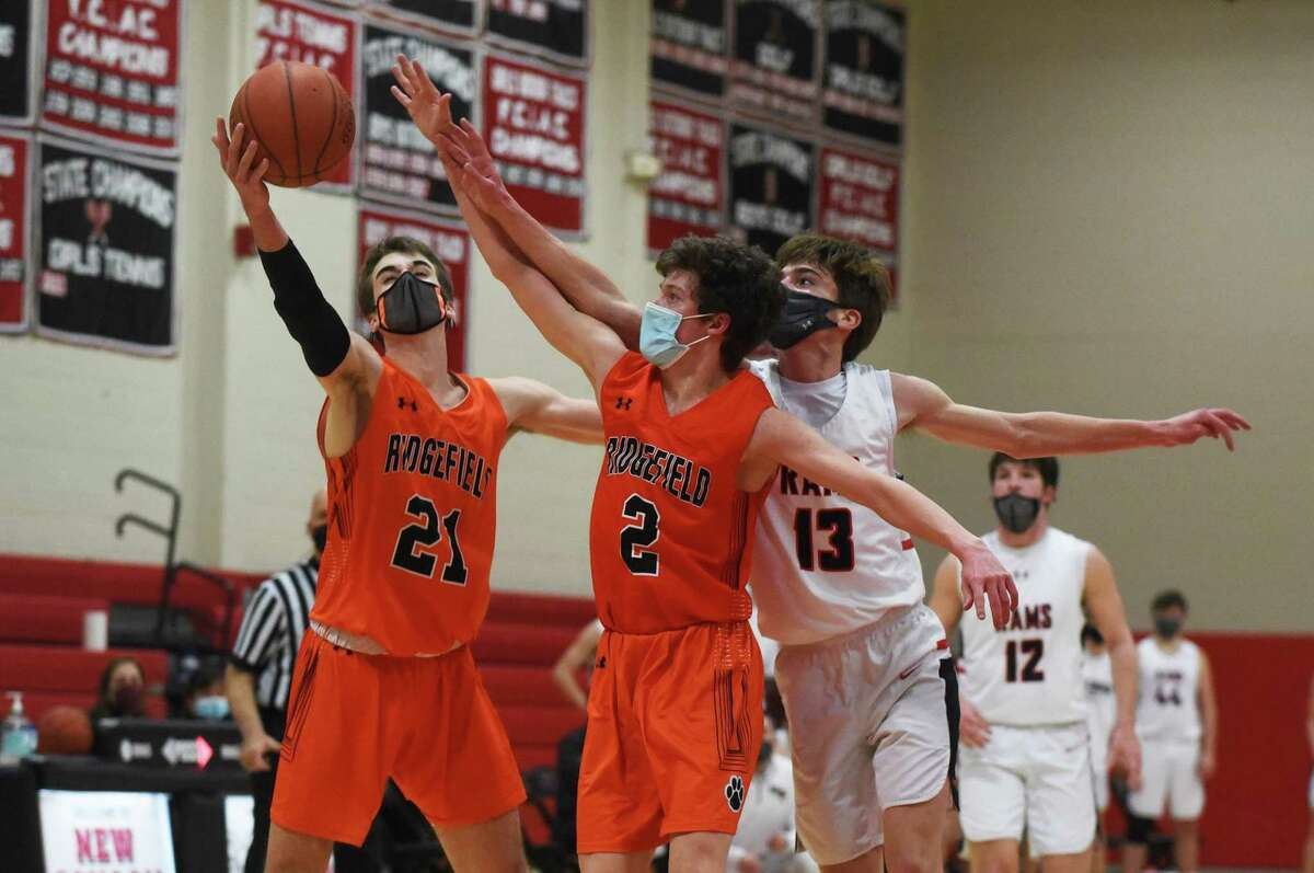 Ridgefield's Emmett O'Malley (21) and Matthew Knachel (2) and New Canaan's Blake Wilson (13) battle for the ball during a boys basketball game at New Canaan High School on Wednesday.