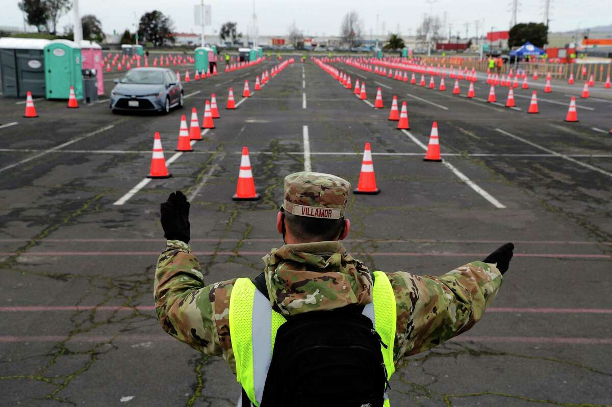 A California National Guard member directs traffic as Pfizer COVID-19 vaccines were administered to the public for the first day of mass vaccinations at the Oakland Coliseum, February 16, 2021.