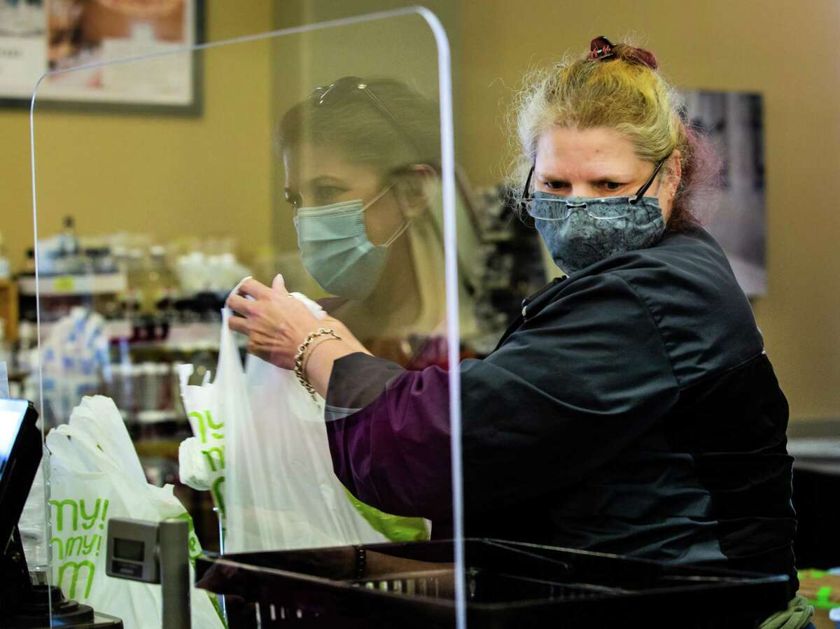 Phoenicia Specialty Food cashier Donna Ross serves guests at the check-out counter while wearing a protective mask during the COVID-19 pandemic, Wednesday, March 3, 2021, in Houston.