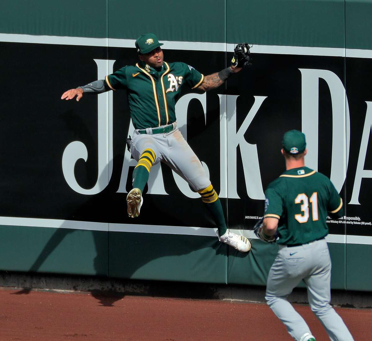 Buddy Reed (72) leaps for a ball at the centerfield wall but the impact caused the ball to come loose from his glove in the fifth ining as the Oakland Athletics played the Colorado Rockies at Salt River Fields at Talking Stick in Scottsdale, Ariz., on Wednesday, March 3, 2021.