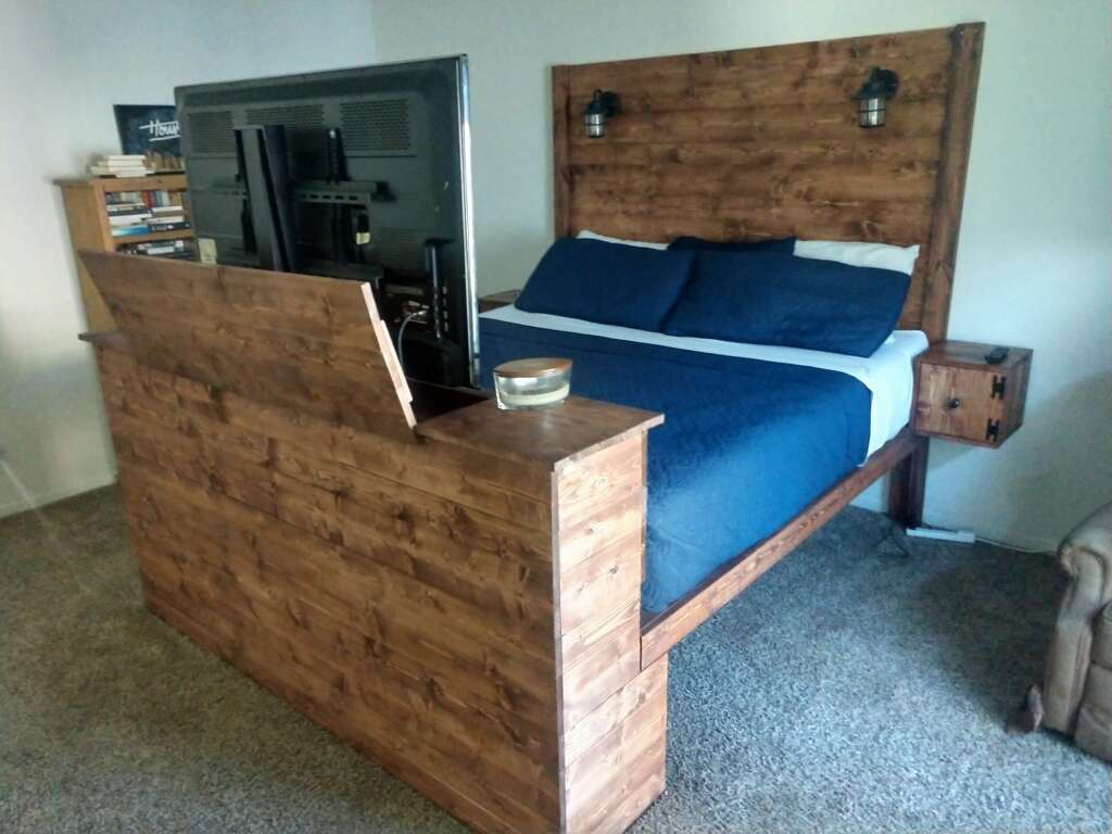 A custom-built wood platform bed frame, featuring a built-in TV lift in the footboard.
