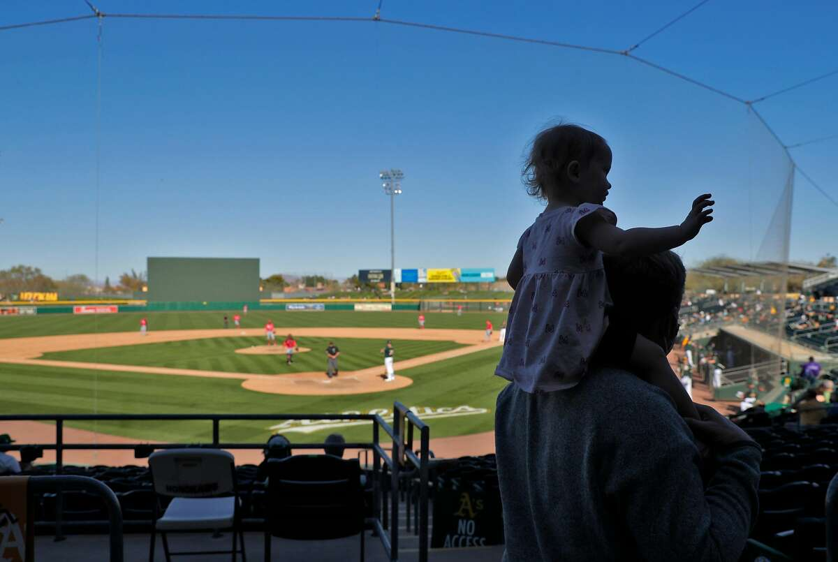 A man walks along the concourse with his daughter on his shoulders as the Athletics play the Reds at Hohokam Stadium in Mesa, Ariz., on Monday.