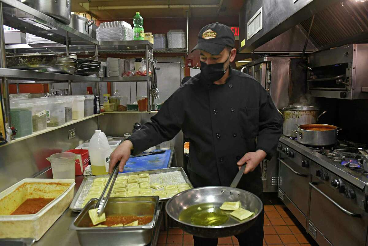 Robert Cardona Jr. makes pan seared ravioli with fresh tomato ragout in the kitchen at Cardona's Market on Wednesday, March 3, 2021 in Albany, N.Y. As it celebrates its 75th anniversary, Cardona's Market is being passed down to the next generation. (Lori Van Buren/Times Union)