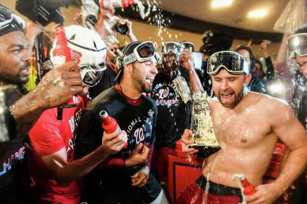 Brian Dozier, who has lost his shirt, celebrates Washington's NLCS win with Howie Kendrick and Aníbal Sánchez.