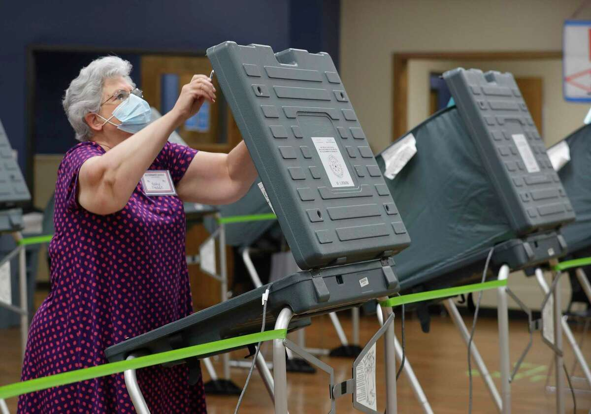 Kathy Trahan wears a facemask as she sets up voting stations before the polls open at the South Montgomery County Community Center, Thursday, July 2, 2020, in The Woodlands. Election officials have implemented several safety and sanitization features to protect voters and polling location volunteers from the coronavirus.